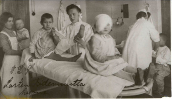 Children and nurses in an early 20th century bandaging room.
